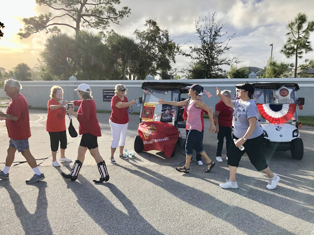 Indian River Colony Club walker Yvonne Tetreault reaches for a water bottle from Marine Wives Club member Phyllis Gautreaux, during the IRCC walk-a-thon to benefit Brevard veterans financially impacted by COVID-19. 60 walkers from the community participated in the fundraiser. photo by Terry Melloy.